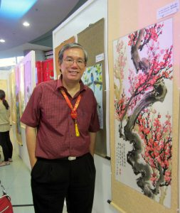 Eng'r Felix Chan Lim poses beside the painting of a plum tree. It's a painting he and brother Alex made. Felix painted the trunk, Alex painted the flowers and the calligraphy.