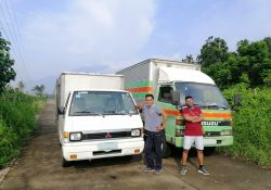 two men pose by an isuzu elf and a smaller container van